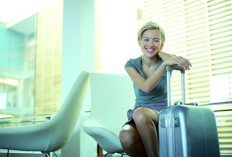 Businesswoman leaning on luggage in office