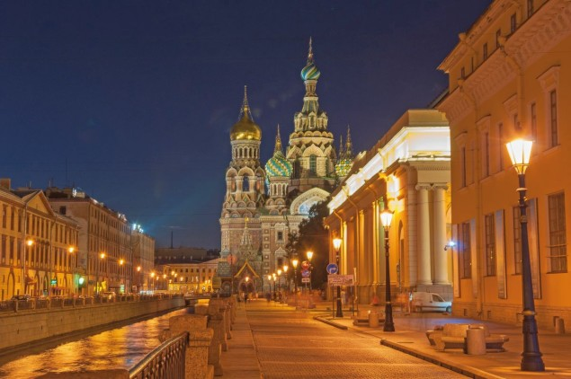 View of the embankment of the city at night from the water of the river Neva.